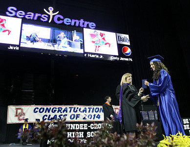 Jeff Krage - For Shaw Media Dundee-Crown High School graduate Stacy Carreon receives her diploma during Saturday's graduation ceremonies at the Sears Centre in Hoffman Estates.