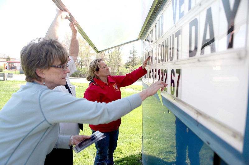 (From left) Kathy Loubsky, volunteer coordinator for the Salvation Army Golden Diners, Salvation Army Major Ken Nicolai and Kolleen Rojas, central kitchen manager, assemble a sign promoting the Salvation Army's Annual Donut Days outside their Geneva facility. Donut Days takes place May 30-31 June 6-7.