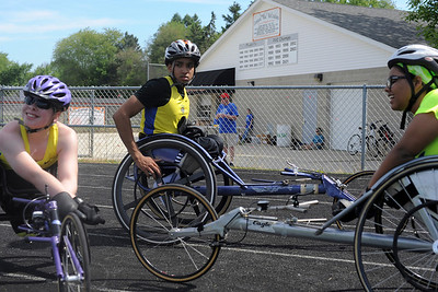 Melanie Watson, of Oconomowoc, Wis., Christan Clemmons, of Waukegan, and Serena Jaros, of Kenosha, Wis., relax after competeing in the 800m wheelchair race during the 7th annual Run and Roll at McKraken Field in McHenry.