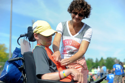 Shane Hammortree, of Marengo, gets his number readjusted by his mother, Annette, during ther 7th Run and Roll Track Meet at McKracken field in McHenry. Saturday was the first time Shane had comepted in any type of organized event.