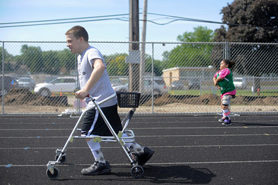 Ben Spengel,16, of Woodstock, races to the finish line during a heat of the 60m dash during the 7th annual Run and Roll Track Meet at McKraken field in McHenry. The meet was started by Spengel who wanted an event in which he and others like him could compete. The meet is also a fundraiser for Spengel's sled hockey team.