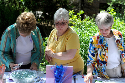 "Kristine Norton, Lory Gregory, both of Cary, and Gale Penn, of Crstyal Lake, make jewelery at a booth during Cancer Survivor days at Centegra Sage Cancer center in McHenry. Norton is a four time cancer survior whom was helped by Gregory during her treatments. "" This day is for those who helped me during that process,"" says Norton about the event."