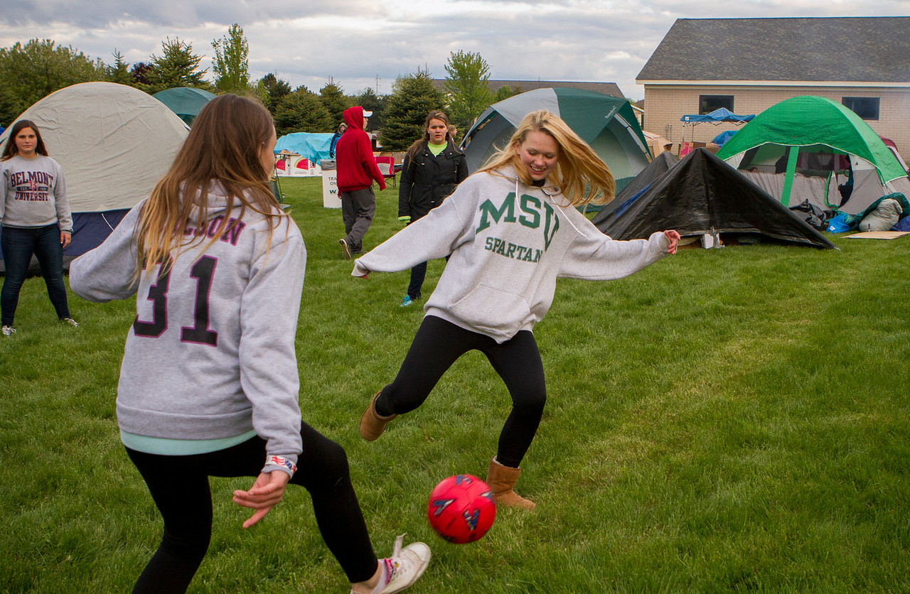 Mike Greene - For Shaw Media  Allison Durham, 15, right of Richmond-Burton High School, attempts to steal the ball while playing keep away with Katelynn Carlson, 15, during the seventh annual SleepOut for Shelter fundraiser hosted by the Pioneer Center Saturday, May 14, 2016 at The Church of Holy Apostles in McHenry. Event participants spent the night outside in tents, boxes or cars to raise awareness and money for McHenry County PADS.