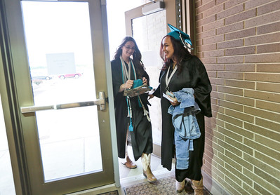 Michelle LaVigne/ For Shaw Media Diana Perez of Wonder Lake holds the door for friend Kristin Lemke (left) of Woodstock as she rushes in after retrieving her tassel from her mother for Woodstock North's High School Graduation ceremony.