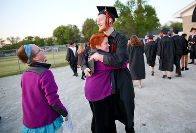 Michelle LaVigne/ For Shaw Media Cody Merritt hugs his sisters nine-year-old Caitlin and 10-year-old Casey Hewett after McHenry East's High School Graduation ceremony.