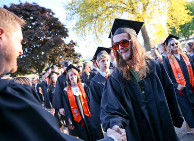 Michelle LaVigne/ For Shaw Media Travis Sandoz extends a handshake to one of his teachers as he prepares to enter the stadium for for McHenry East's High School Graduation ceremony.