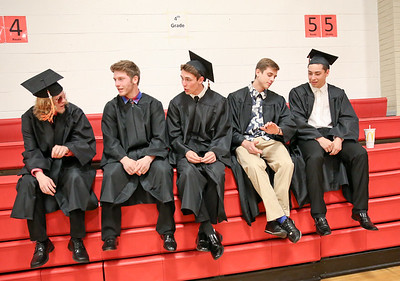 Michelle LaVigne/ For Shaw Media Left to right, Jeremiah Jayhan of Lakemoor, Dylan Mizer of McHenry, Isaak Carlton of McHenry, Gabriel Stanaszek of Fox Lake and Carter Garbacz of Lakemoor talk with each other as they wait to line up for for McHenry East's High School Graduation ceremony.