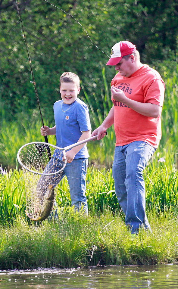 Candace H. Johnson Eli Welch, 10, of Antioch is all smiles as his father, Mike, holds the fish he caught in a net during the Lindenhurst Park District's annual Carp Fishing Derby at John Jenega Memorial Park in Lindenhurst.