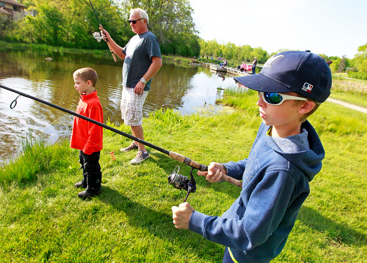 Candace H. Johnson Reese Mock, 6, of Lindenhurst and Patrick Schmidt, of Spring Grove stand close to Cole Covert, 9, of Lindenhurst while they fish during the Lindenhurst Park District's annual Carp Fishing Derby at John Jenega Memorial Park in Lindenhurst.