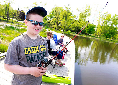 Candace H. Johnson Max Krieger, 12, of Lake Villa fishes next to his mother, Dena, and brother, Sam, 10, during the Lindenhurst Park District's annual Carp Fishing Derby at John Jenega Memorial Park in Lindenhurst.