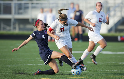 Taryn Jakubowski (11) of Huntley is fouled by Arielle Walters (4) of South Elgin during the first half of the Streamwood Class 3A Girls Soccer Sectional on Thursday, May 26, 2016 in Streamwood, Illinois. Jakubowski scored a point on the penalty shot and the Red Raiders defeated the Storm 2-1.  John Konstantaras photo for the Northwest Herald