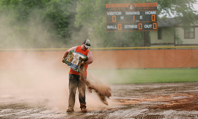 Dan Strickfaden spreads Quick Dry on the infield before the Class 4A McHenry Regional softball final between Prairie Ridge and Crystal Lake Central on Friday, May 27, 2016 in McHenry. The game was rescheduled for Saturday at 2pm.  John Konstantaras photo for the Northwest Herald