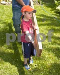 Five year old Joe Grussenmeyer helps bring boards out that will help outline the garden edge. David Toney for Shaw Media