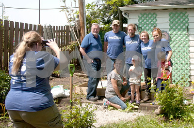Garden Works Project volunteers pose for a photo with the Mayor of Wheaton (far left) during Saturday's 100th Garden Works Project build. David Toney for Shaw Media