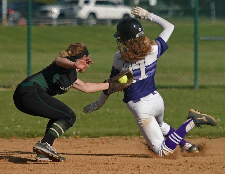 Kayla Wolf for Shaw Media- Hampshire sophomore Morgan Haefling attempts to avoid the tag by Bishop Mac second baseman Tonya Faulkner . Bishop McNamara won 6 to 2.
