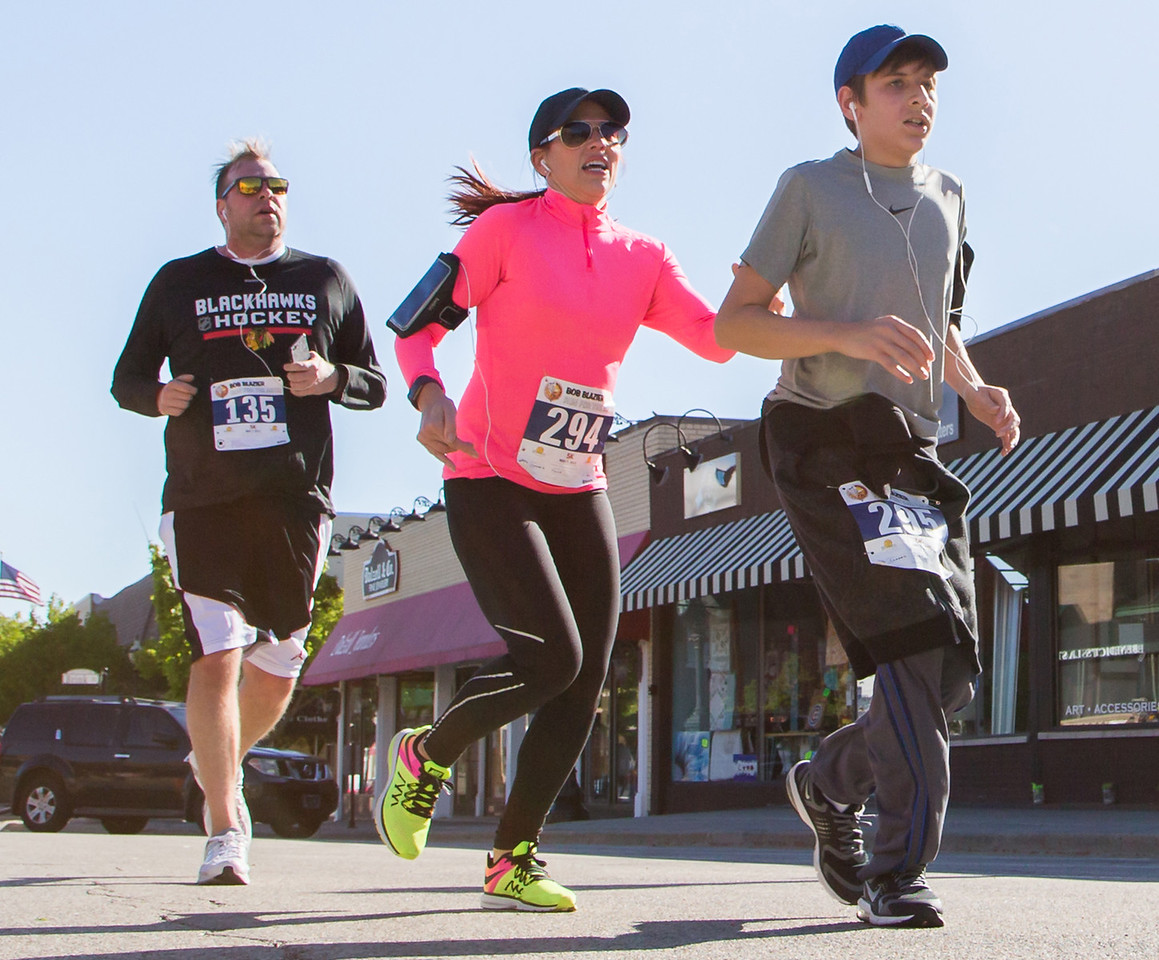 Ken Koontz – For Shaw Media Runners Murray Crabtree (from left) Tania Suarez and Raef Suarez cross the finish line in the 20th annual Bob Blazier Run for the Arts 5K Run and Walk on May 7 in Crystal Lake.