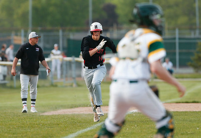 Adam Smylie (center, 14) from Huntley tags up a scores on a sacrifice fly hit by Bradley Maurer (not pictured) before tagging up to score during the fourth inning of their game against Crystal Lake South on Monday, May 15, 2017 in Crystal Lake. The Red Raiders won the game 2-0. | John Konstantaras photo for the Northwest Herald