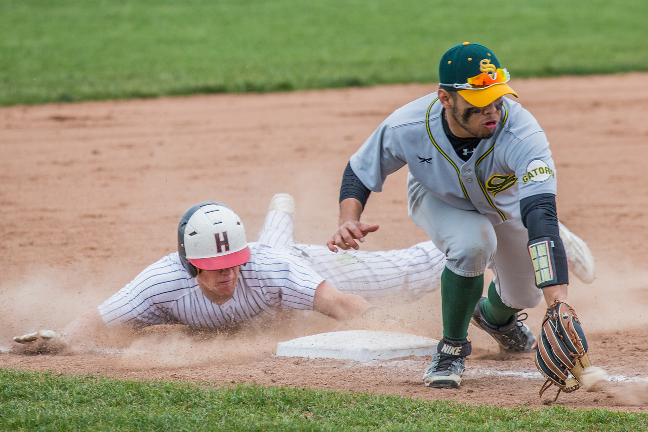 Huntley's Jeffrey Heinrich (Left) slides into third base on a wide throw to Crystal Lake South third baseman Brian Fuentes Reyes (right). Huntley went on to win in extra innings Saturday, May 13, 2017 at Huntley High School KKoontz – for Shaw Media