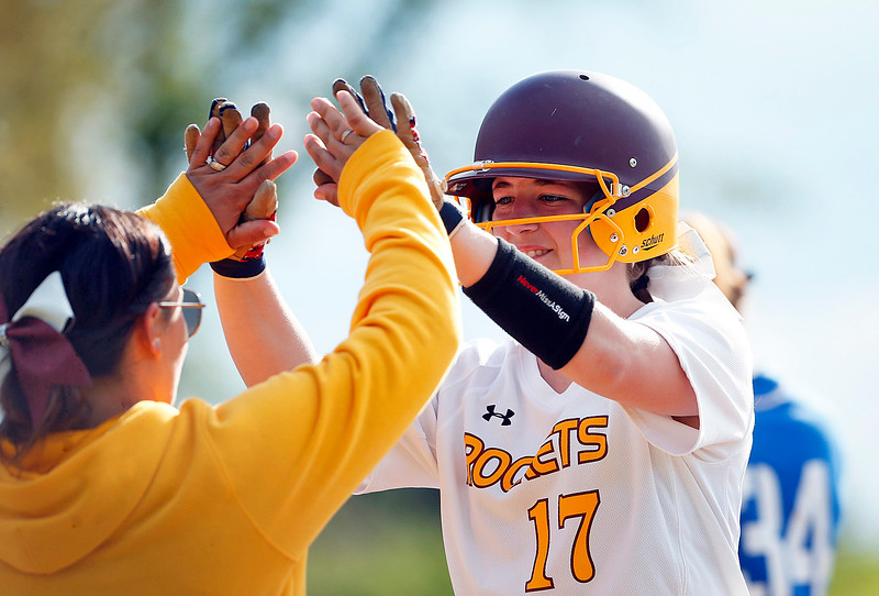 Abby Hayden (17) from Richmond-Burton high fives her first base coach after batting in a run during the third inning of their game against Woodstock at Richmond-Burton High School on Thursday, May 18, 2017 in Richmond. The Rockets defeated the Blue Streaks 12-2 in 5 innings. John Konstantaras photo for the Northwest Herald