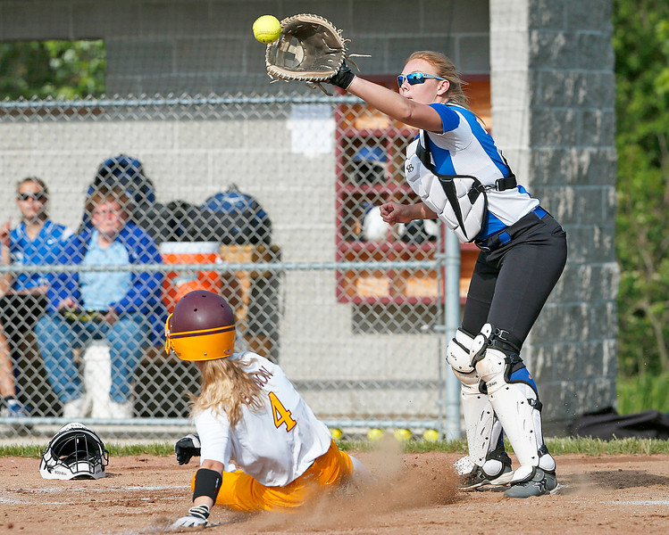 Peyton Bannon (4) from Richmond-Burton slides in ahead of the tag by Julia Vosburgh (24) from Woodstock during the first inning of their game at Richmond-Burton High School on Thursday, May 18, 2017 in Richmond. The Rockets defeated the Blue Streaks 12-2 in 5 innings. John Konstantaras photo for the Northwest Herald