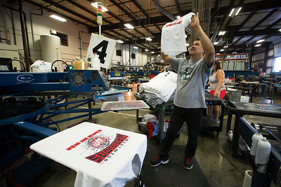 John Konstantaras - For Shaw Media Rodolfo Valencia of Crystal Lake, check a screen printed shirt at Sport Decals on Thursday, May 18, 2017 in Spring Grove. Paul Metivier, Chris Gagnon and Don Metivier have recently re-acquired the company serves more than 10,000 high schools, colleges, clubs and organizations through the sale of custom team uniforms, spirit wear and decals.  John Konstantaras photo for the Northwest Herald