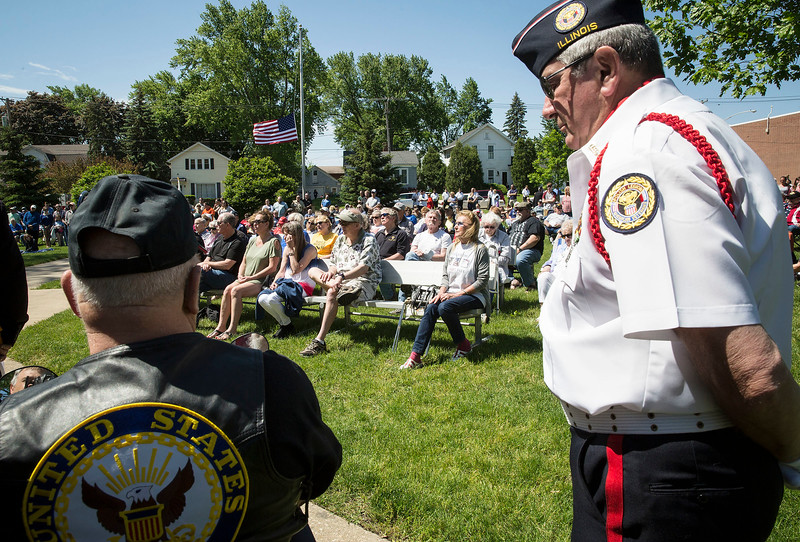 Participants listen as Gary Snell, not pictured, reads the names of deceased military members during the Memorial Day ceremony at Veterans Memorial Park on Monday, May 29, 2017 in McHenry. John Konstantaras photo for the Northwest Herald