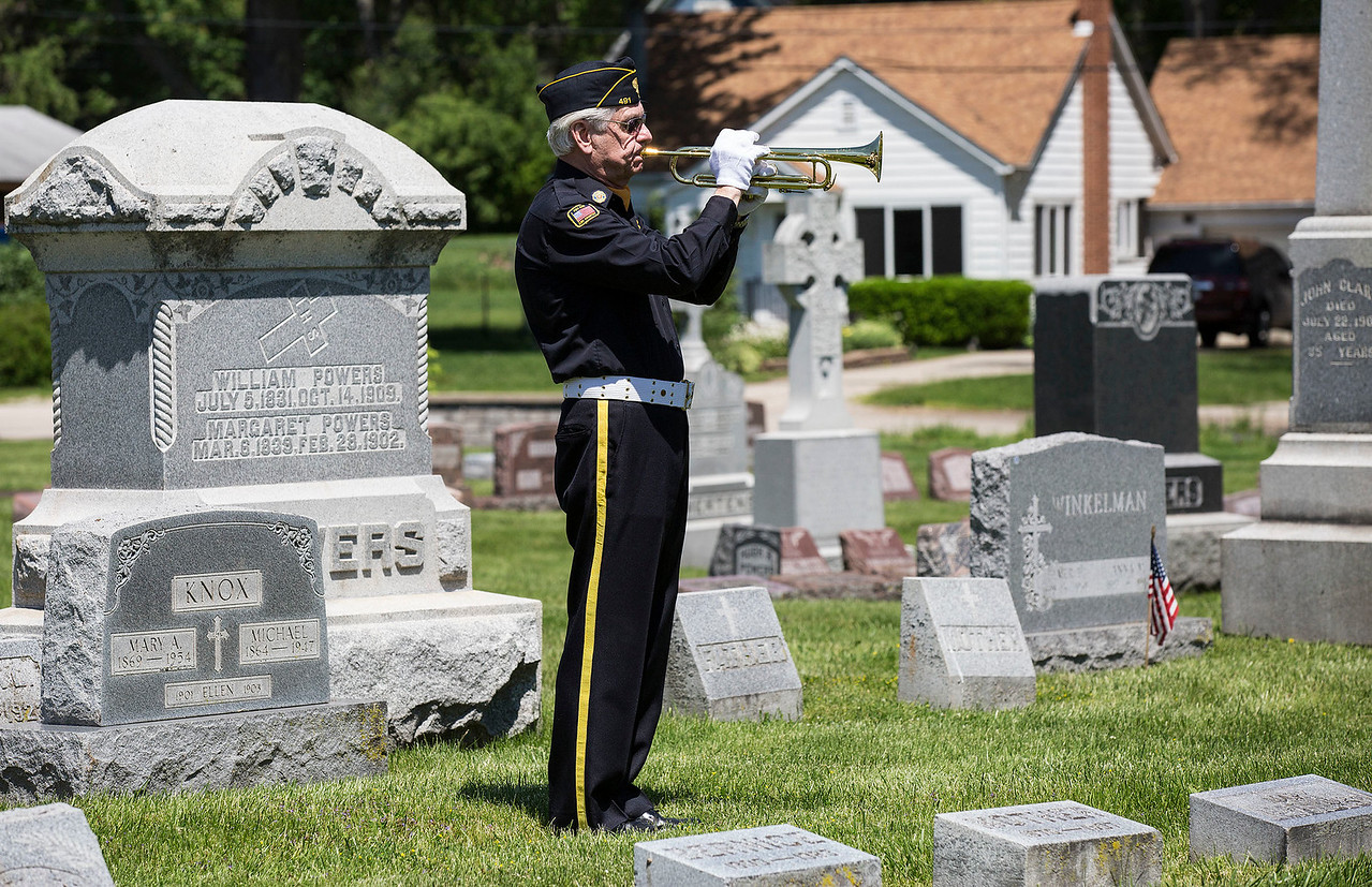 Air Force Veteran Ron Bukowski, with American Legion Post 491, plays taps at the St. Patrick's Parish Cemetery during Memorial Day Monday, May 29, 2017 in McHenry. John Konstantaras photo for the Northwest Herald