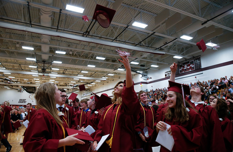 Jessica Blaschek, center, tosses her cap while Emily Bolash hold her daploma after commencement ceremonies at Richmond-Burton High School on Sunday, May 21, 2017 in Richmond.  John Konstantaras photo for the Northwest Herald
