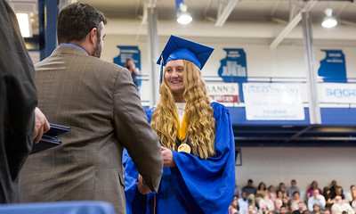 Mike Greene - For Shaw Media  Class Valedictorian Shannon Fetzner receives her diploma during graduation ceremonies for Woodstock High School Sunday, May 21, 2017 in Woodstock.