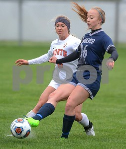 Oswego East senior Taylor Peck kicks the ball away from Naperville North's Alyssa Siebers during their Class 3A Regional final game May 19 at Oswego High School. Mark Busch - mbusch@shawmedia.com