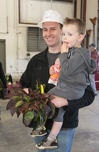 Candace H. Johnson-For Shaw Media Dan Heideman, of Round Lake carries his son, Luke, 2, after getting a free plant and popcorn during the Arbor Day Celebration at the Village of Round Lake Police and Public Works facility on Townline Road in Round Lake.(4/28/18)