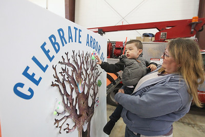 Candace H. Johnson-For Shaw Media Audrie Poulsen, of Lake Villa holds Kilian Nowicki, 2, of Cary as he puts a hand craft he colored on a Celebrate Arbor Day poster during the Arbor Day Celebration at the Village of Round Lake Police and Public Works facility on Townline Road in Round Lake.(4/28/18)