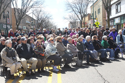 Candace H. Johnson-For Shaw Media A crowd watches the Trail Marker Tree bronze sculpture Installation and Dedication on Main Street in Antioch.The sculpture was made by local artist Dennis Downes and stands in a mini-park next to JJ Blinkers on Main Street.(4/28/18)