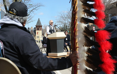 Candace H. Johnson-For Shaw Media Joe Yazzi, of Carpentersville, a Navaho Apache Indian, holds an Eagle staff as he listens to local artist Dennis Downes talk about the Trail Marker Tree bronze sculpture he made during the Installation and Dedication of the sculpture on Main Street in Antioch.The sculpture stands in a mini-park next to JJ Blinkers on Main Street.(4/28/18)