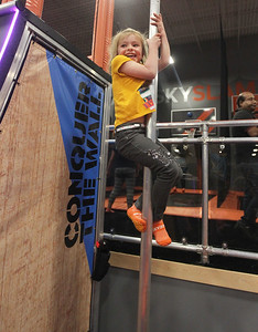 Candace H. Johnson-For Shaw Media Molly Huhn, 5, of Volo slides down the pole after running up the Warped Wall during the grand opening celebration of the Sky Zone indoor trampoline park in Vernon Hills.(4/24/18)