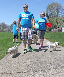 Candace H. Johnson-For Shaw Media Albert and Heather Malik, of Lake Villa walk with their dogs, Cooper and Tucker, during the free Go Grayslake Community Walk in Central Park in Grayslake.The event was sponsored by the Grayslake Community Park District.(5/6/18)