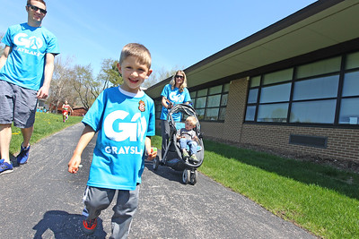 Candace H. Johnson-For Shaw Media Michael and Kayla Canino, of Grayslake and their sons, Joey, 4, and Keaton, 2, (in stroller) walk on the trail next to the Grayslake Middle School during the free Go Grayslake Community Walk in Central Park in Grayslake.The event was sponsored by the Grayslake Community Park District.(5/6/18)