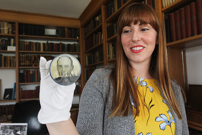 "Candace H. Johnson-For Shaw Media Nicole Stocker, museum educator, holds up a political button with Adlai Stevenson's picture and the slogan, ""All the Way with Adlai,"" he used during his presidential campaigns in 1952 and 1956, on display at the Adlai E. Stevenson II Historic Home located in the Captain Daniel Wright Woods Forest Preserve in Mettawa. (5/3/18)"