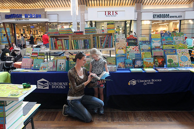 """Candace H. Johnson-For Shaw Media Kahla Dunn, of Gurnee reads a """"Horses & Ponies"""" book to her daughter, Tessa, 5, in the Usborne Books & More booth during the Spring Craft Fair at Gurnee Mills. David Slotnik, of Island Lake sold the books in the booth.(5/6/18)"""