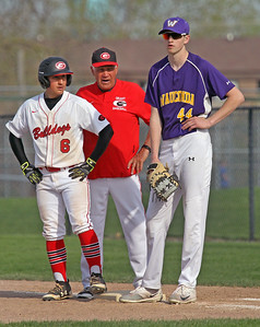 Candace H. Johnson-For Shaw Media Grant's Valentin Cerna listens to Coach Fritz Kazlausky as he makes it to first while standing next to Wauconda's Clark Morgan in the second inning at Grant Community High School in Fox Lake. Wauconda won 9-3.