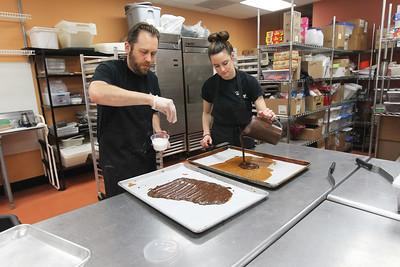 Candace H. Johnson-For Shaw Media Jason Mule, head chocolatier, sprinkles sea salt and Caitlin Matic, both of Grayslake, pours the chocolate as they make dark chocolate sea salt toffee in the kitchen at Uniquely Sweet on Belvidere Road in Grayslake.(5/15/18)