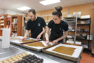 Candace H. Johnson-For Shaw Media Jason Mule, head chocolatier, and Caitlin Matic, both of Grayslake use paper towels to wipe off excess butter from freshly made toffee to be able to put chocolate on it once it cools in the kitchen at Uniquely Sweet on Belvidere Road in Grayslake.(5/15/18)