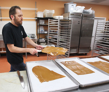 Candace H. Johnson-For Shaw Media Jason Mule, of Grayslake, head chocolatier, takes thin layers of freshly made toffee to trays as he makes  base toffee to create different flavors in the kitchen at Uniquely Sweet on Belvidere Road in Grayslake.(5/15/18)