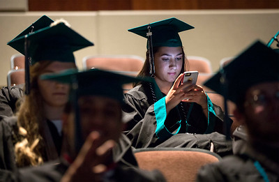 Isabella Villalva checks her phone as she waits with her fellow graduates before the Woodstock North High School graduation on Saturday, May 19, 2018 in Woodstock, Illinois. John Konstantaras photo for Shaw Media