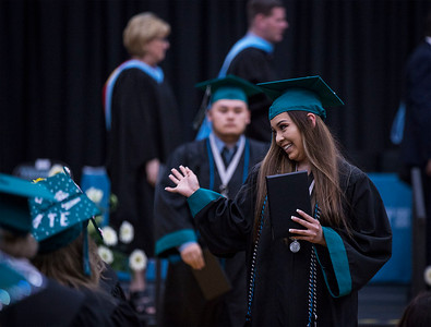 Ashley Mendoza waves to a friend after receiving her diploma during the Woodstock North High School graduation on Saturday, May 19, 2018 in Woodstock, Illinois. John Konstantaras photo for Shaw Media