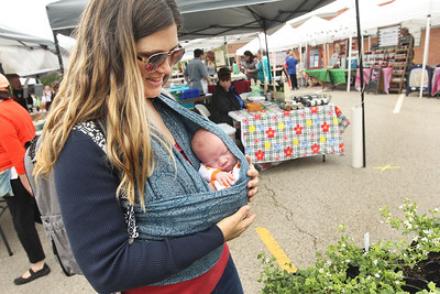 Candace H. Johnson-For Shaw Media Ashley Bonnes, of Grayslake carries her son, Wyatt, two and a half weeks old, as she stops to look at the flowering plants for sale by Geneva Lakes Produce at the Spring Grayslake Farmers Market on Center Street in downtown Grayslake. The Spring Market runs on Saturdays through May 26th from 10-2:00 pm. and the Summer Market runs on Wednesdays May 30- September 26 from 3-7:00 pm. (5/19/18)