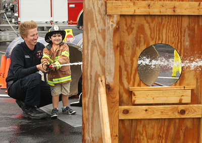 Candace H. Johnson-For Shaw Media Fire Medic Clint Herdegen with the Wauconda Fire District helps Ryan Piraka, 4, of Gurnee hit his target using a fire hose during the 21st Annual Fire Safety Expo at Gurnee Mills.(5/19/18)