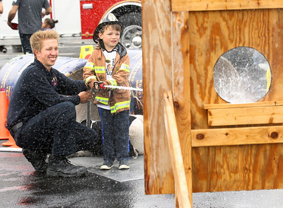 Candace H. Johnson-For Shaw Media Fire Medic Clint Herdegen, with the Wauconda Fire District, helps Henry Sorenson, 5, of Libertyville hit the target using a fire hose during the 21st Annual Fire Safety Expo at Gurnee Mills.(5/19/18)