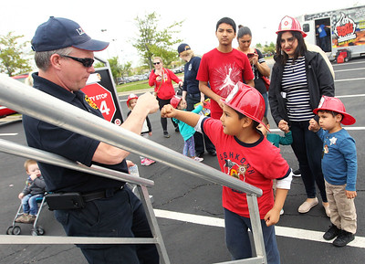 Candace H. Johnson-For Shaw Media Keith Hohs, a Lake Zurich firefighter paramedic, gives a fist bump to Freddy Gama, 6, of Waukegan before he goes down the fire pole during the 21st Annual Fire Safety Expo at Gurnee Mills.(5/19/18)