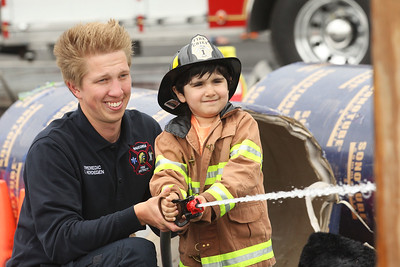 Candace H. Johnson-For Shaw Media Fire Medic Clint Herdegen with the Wauconda Fire District helps Ryan Piraka, 4, of Gurnee hit the target with a fire hose during the 21st Annual Fire Safety Expo at Gurnee Mills.(5/19/18)